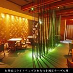 幻想的にライトアップされた竹を囲むテーブル席